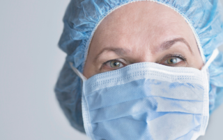 A Doctor with a hair cap and mask with serious looking eyes.