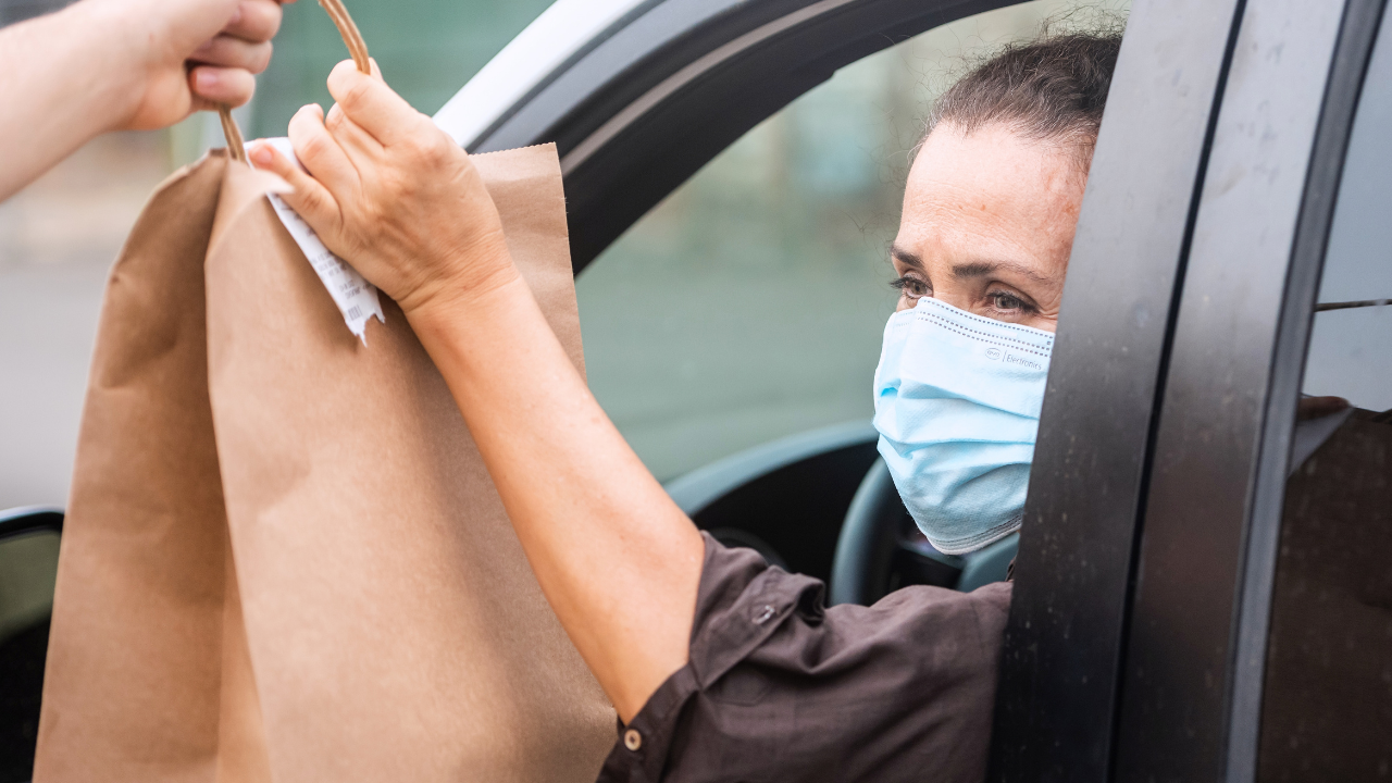 A female wearing a mask is sitting in her car with the window down and taking a brown bag that is being handed to her from outside the vehicle.