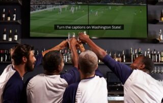 A group of sports fans in a bar. Their backs visible and holding up their drinks to the TV with captions displayed.