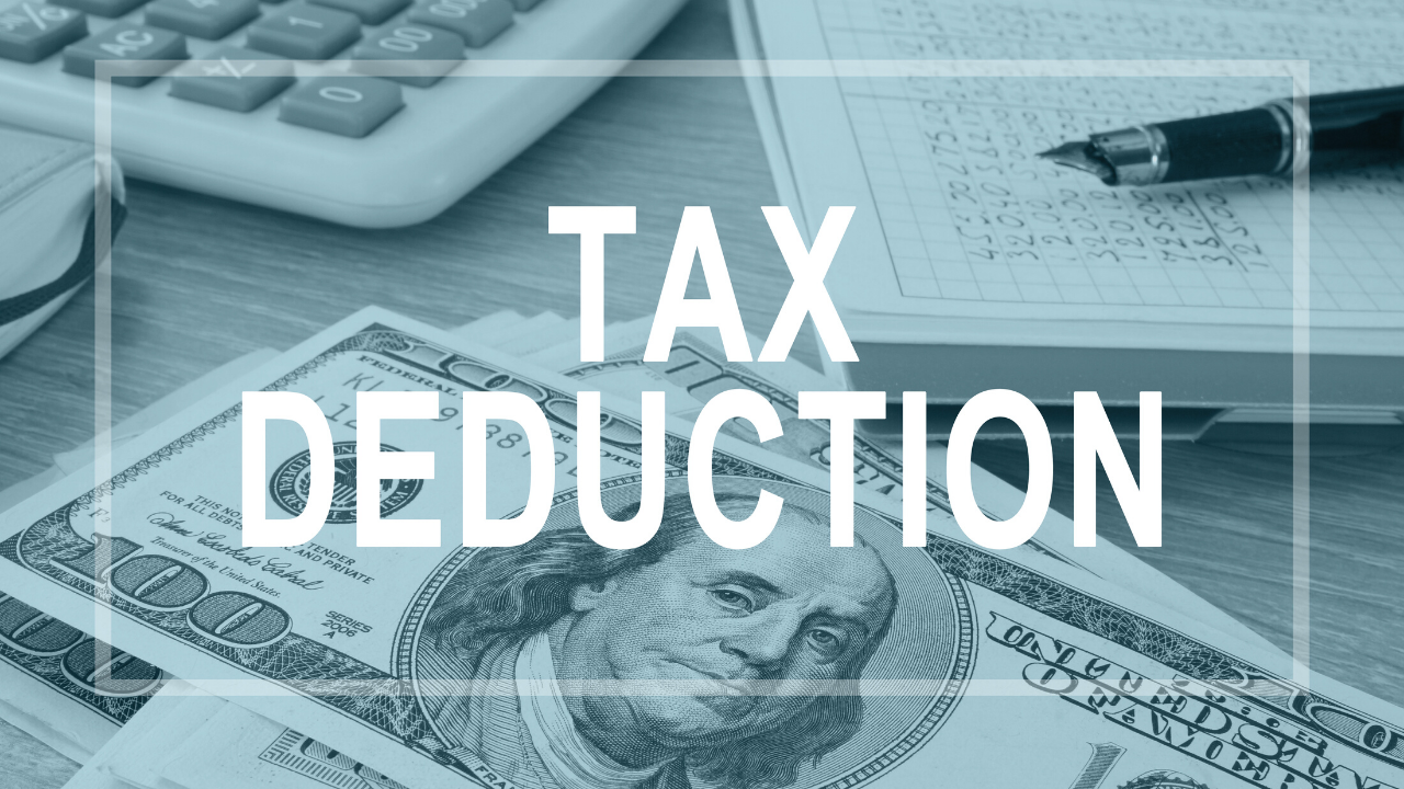 A $100 US Dollar, a calcuator and a pen and pad of paper sit at a desk with a teal overlay and white letting reading TAX DEDUCTION