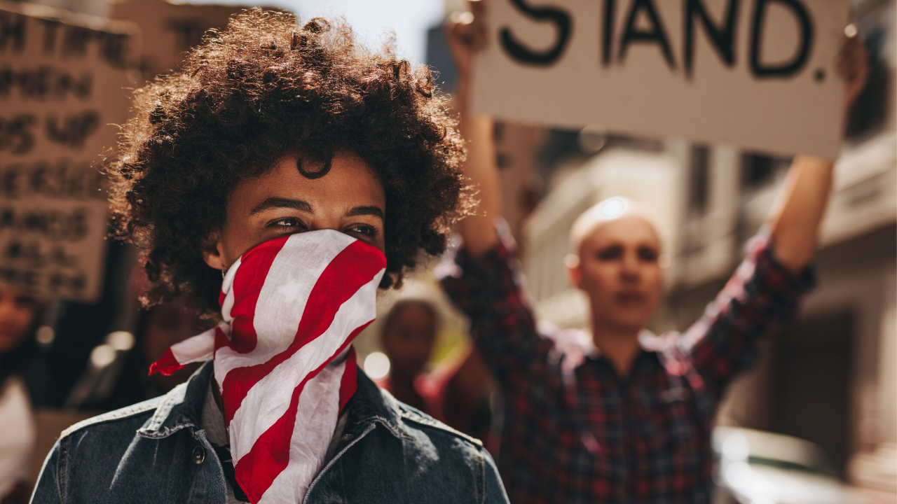 A Black woman with an american flag covering her mouth. Protesters stand behind her holding signs and marching.