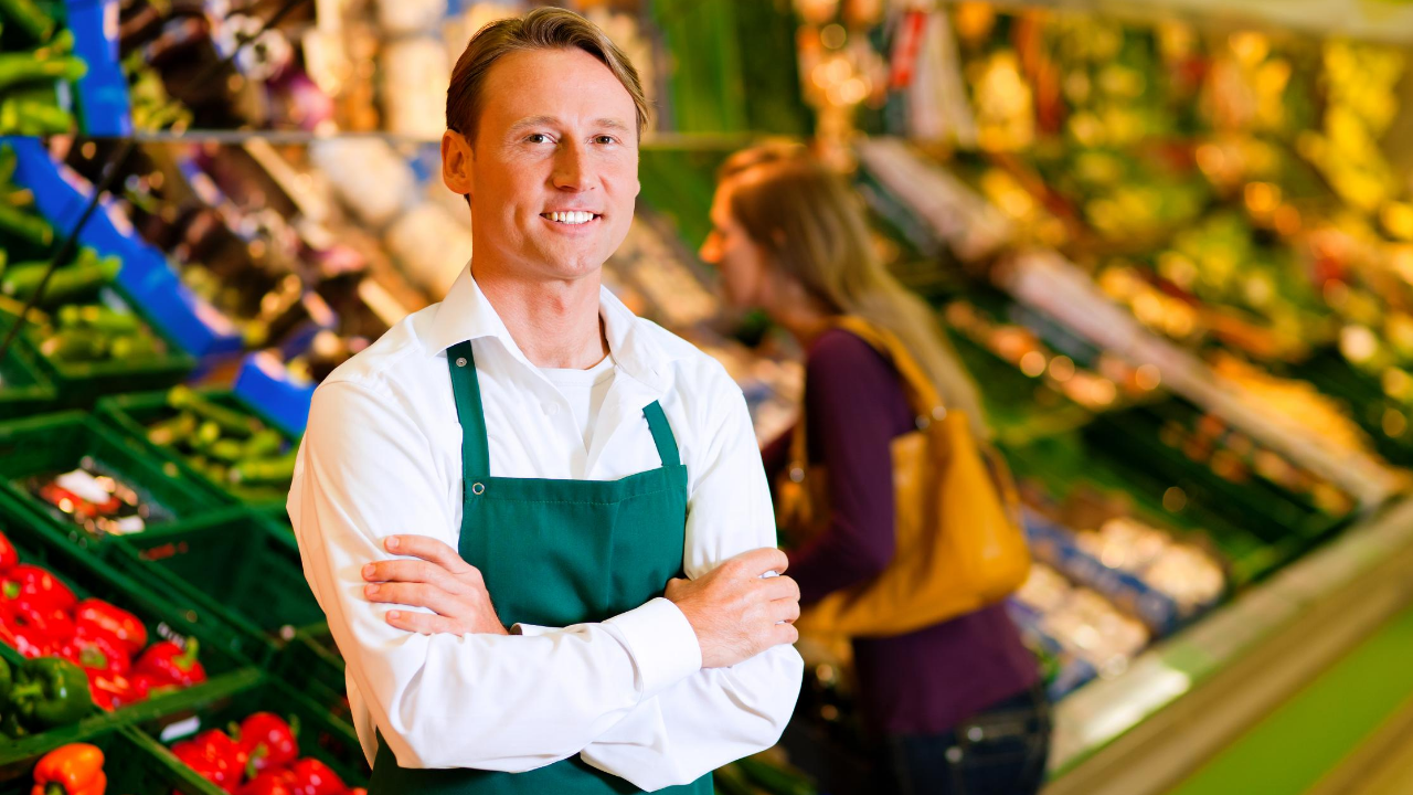 A light skinned male with brown hair working in a grocery store standing in front of the produce smiling.