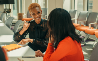 A black deaf woman has short curly bronze-colored hair and is wearing a black top. She is communicating using sign language with a woman with dark shoulder-length hair and a red sweater. Her back is turned to the camera and they are sitting at a large conference table.