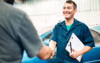 An auto mechanic holding a binder with a blue car in the background is shaking the hand of a customer.